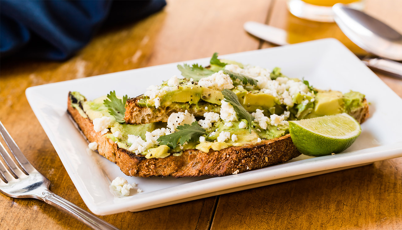Avocado toast - wheat, feta, cilantro, lime, cracked pepper.