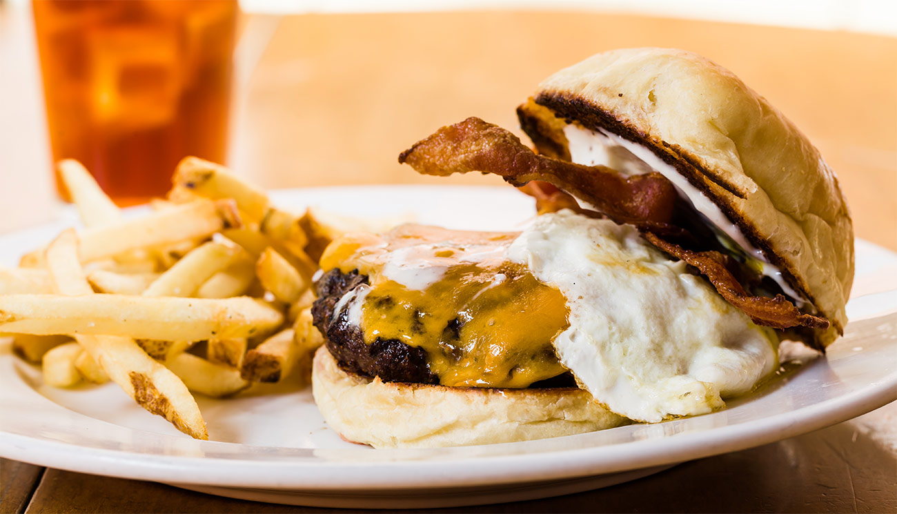 Bacon, egg & cheddar burger on brichoe bun w/ aioli.