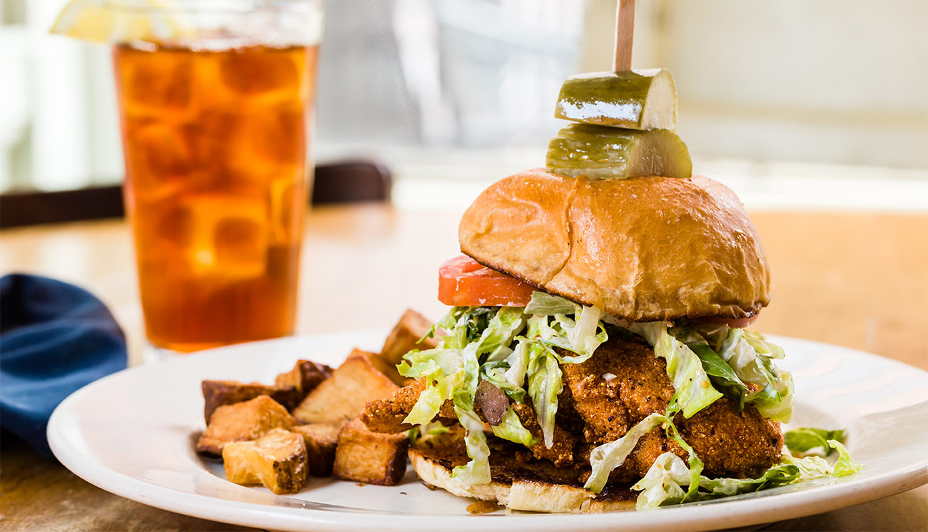 Hot fried chicken - chili oil, lettuce, aioli on brioche bun w/ house pickles.