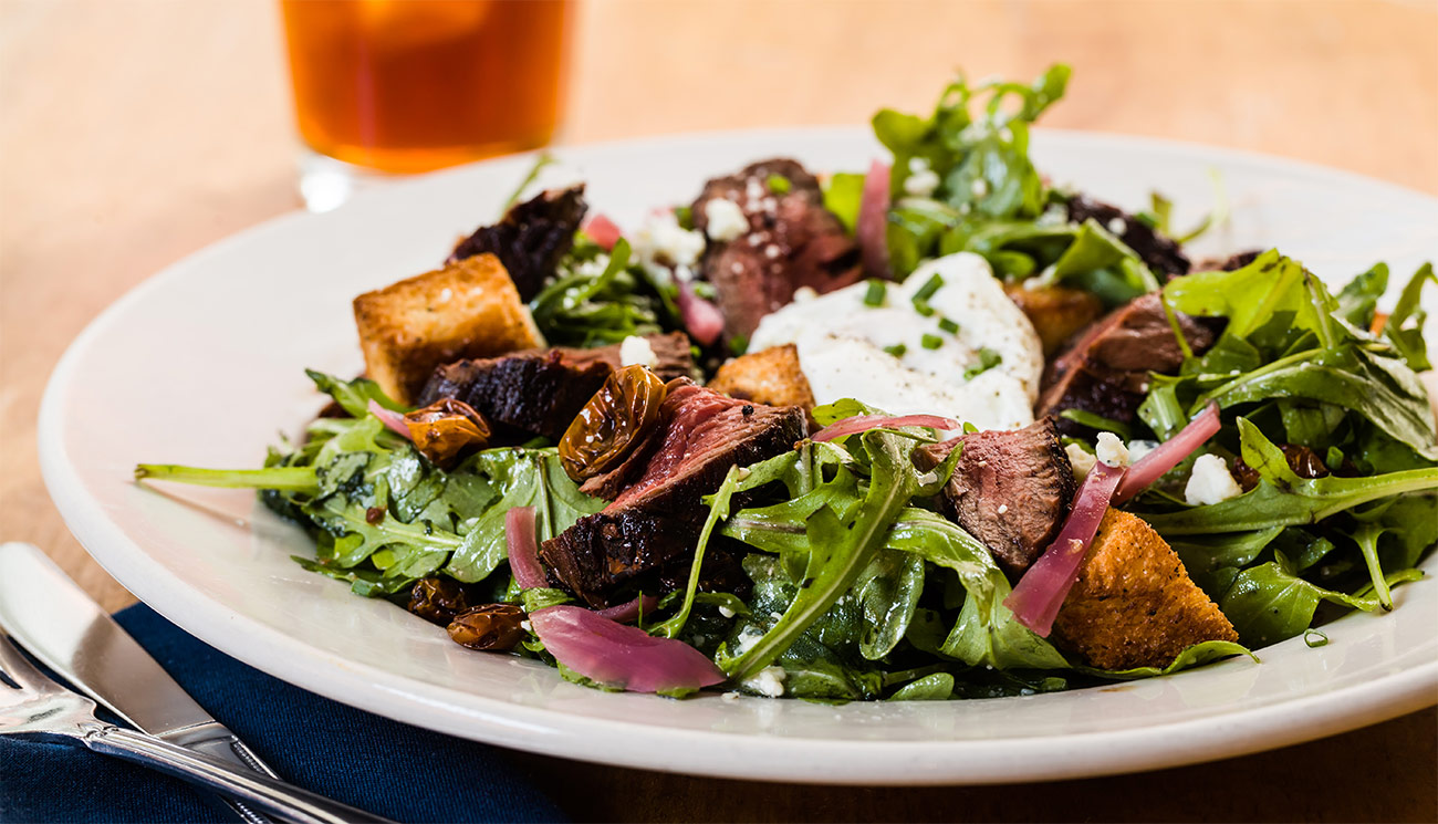 Steak salad - arugula, hanger, poached egg, pickled red onion, cherry tomato, bleu cheese, brioche, red wine vinaigrette.